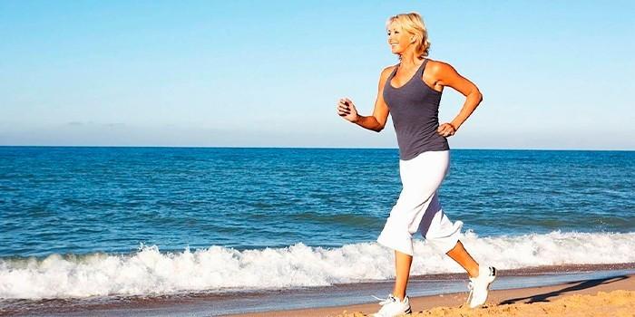 Женщина бежит вдоль побережья