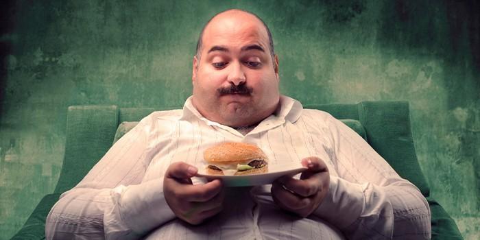 Тучный мужчина с гамбургером